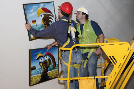 Conservation manager Eric Archer and Locations Registrar Patrick Baum recover paintings from the wall of the Administration corridor.
