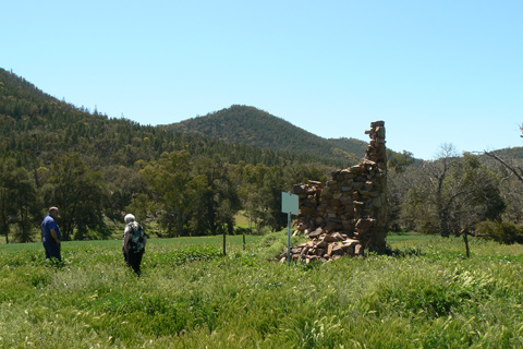 Remains of a stone structure in the centre of a green field, with hills in the background.