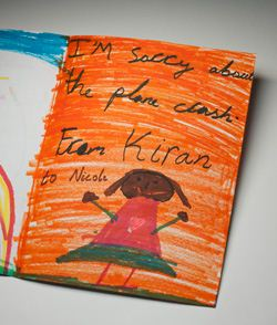 A handmade card showing the right inside view. The background is coloured in orange texta, with the handwritten words 'I'm sorry about the plane crash. From Kiran to Nicole' at top. There is a picture of a girl at the bottom of the card. She wears a pink top with a central heart motif, and a green skirt. She is smiling and her arms are stretched open.