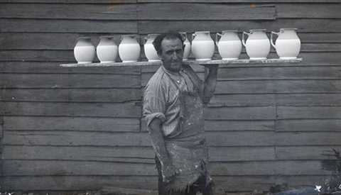 Photograph of Pottery employee H Dower carrying a board laden with jugs.
