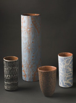 Four cylindrical vases in shades of brown and blue.