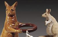 Ochre-glazed stoneware kangaroo, with paws extended round a ring.