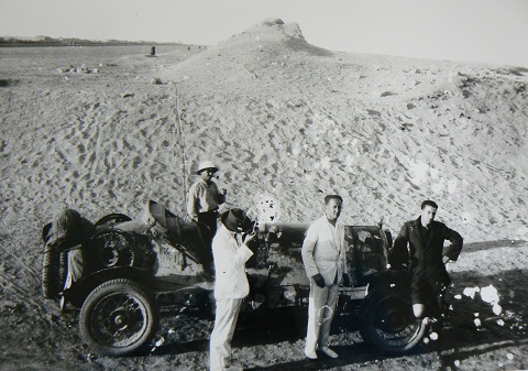 Black and white image showing four men standing beside an open-topped car in the desert. A sand dune rises above the men in the background.