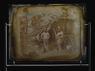 A piece of glass showing a photograph of two men standing outside a bark slab hut.