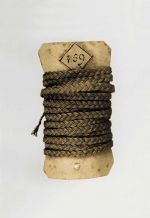 Cord made of made from light brown plant fibres and wound round a thin piece of cardboard.