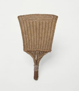 Fan made of pandanus leaves, coconut fibres and wood. The leaves woven to create a pattern consisting of triangles.