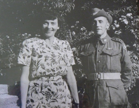 A black and white photograph of a man and a woman. The woman stands at the left of the photo, wearing a dress with a floral print. She has dark hair, and smiles. The man stands at the right of the photo, wearing a Second World War-era army uniform and slouch hat. He has his hands behind his back. Behind them both are large flowering shrubs and bushes.