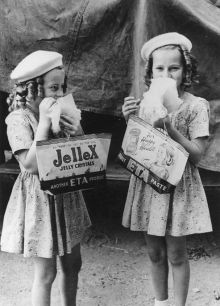 Two young girls eat a treat while holding show bags. One reads 'Jellex Jelly Crystals'; the other 'Peanut ETA Paste'.