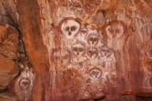 Colour photograph showing Aboriginal art on a rock wall. Numerous faces with oversized eyes and no mouth are depicted on the rock, in shades of yellow, red, black and white.