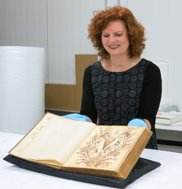 Woman with wavy red hair viewing an open book on a large table