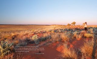 Songlines catalogue spread with a quote from Kumpaya Girgirba and a large desert landscape image