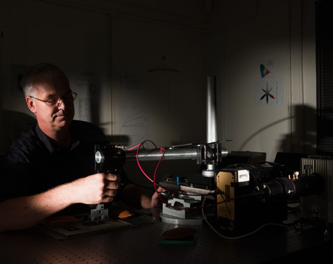 A colour photograph of a museum technician using specialist equipment to test the light sensitivity of an object. The technician sits at the left of the photograph, facing toward the right. On a table in front of him is the equipment, which appears to consist of a horizontal arm that is positioned over the object which is held in place on a special jig. Several wires are connected to the equipment. The photograph has dramatic lighting that has thrown some areas of it into deep shadow.