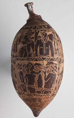 A large boab tree nut with images carved onto its surface. The nut is arranged so that it is vertical ie the ends of the nut are at the top and bottom of the photograph. The images carved onto the nut's surface show people, both Indigenous and non-Indigenous, in a range of settings. The carvings are in two main bands running around the nut. Each band is separated from the other by smaller bands of regular geometric patterns.