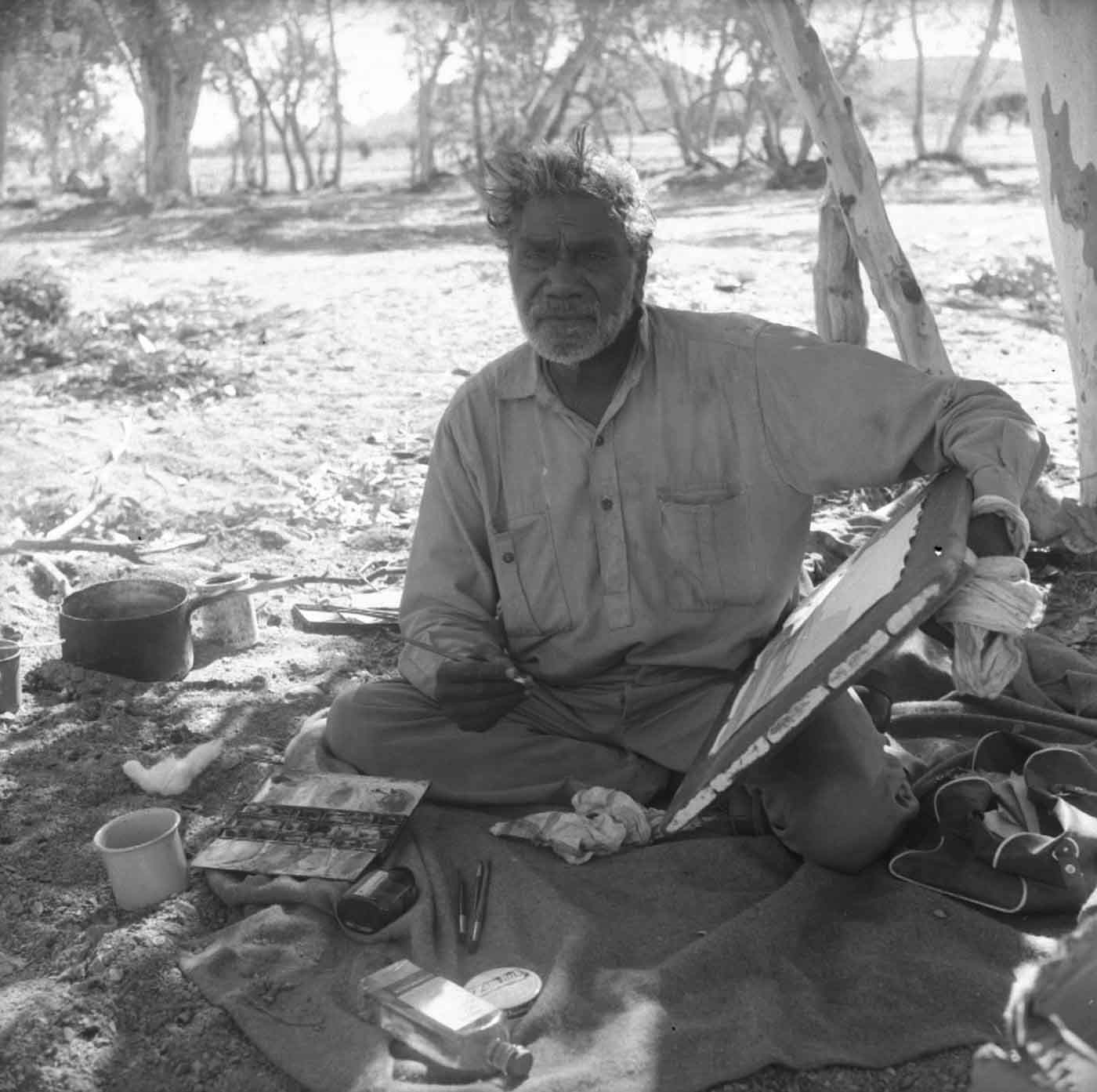 Black and white photo of a man sitting on the ground and painting in bush land.