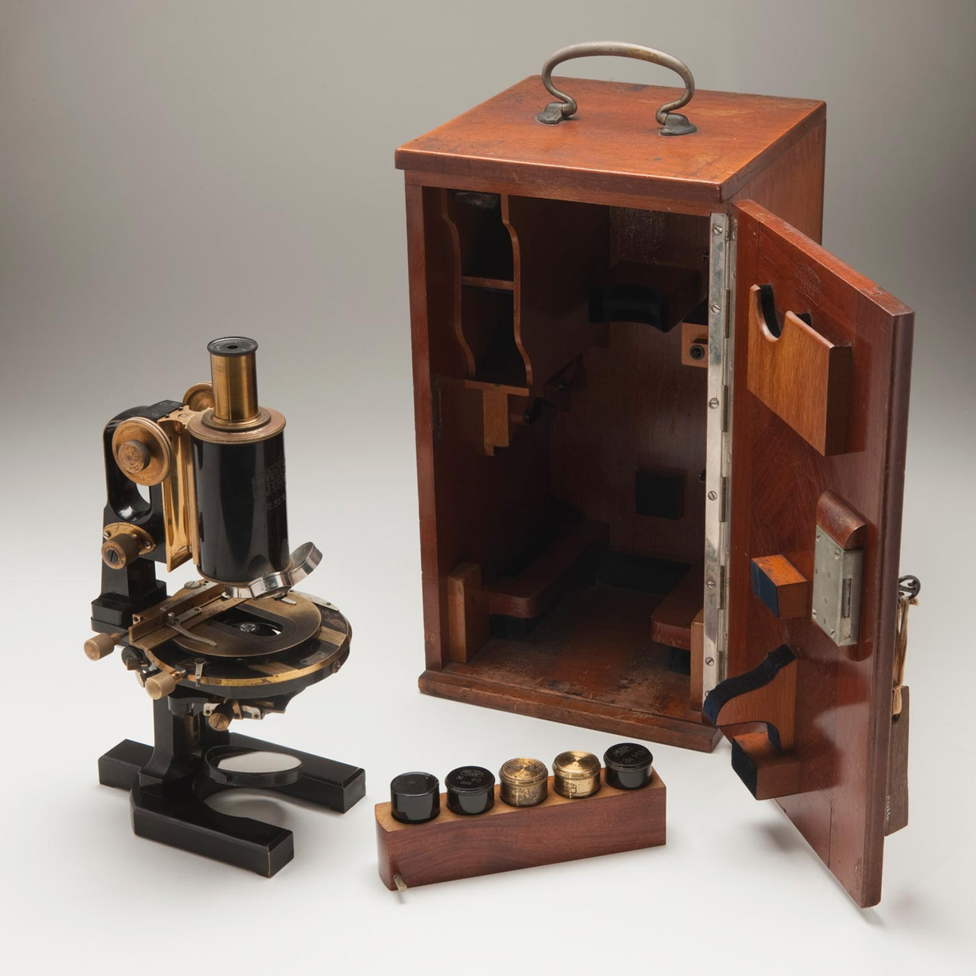A small black telescope with brass fittings sits outside its wooden storage box.