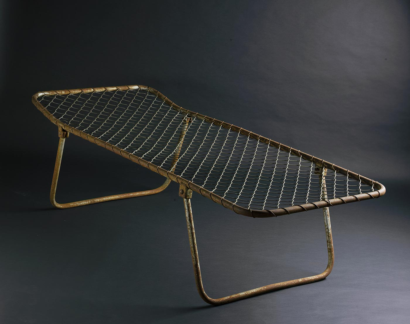 A simple bed with a metal frame, raised slightly at one end. The top of the frame is covered with wire mesh and there are two folding legs underneath. - click to view larger image
