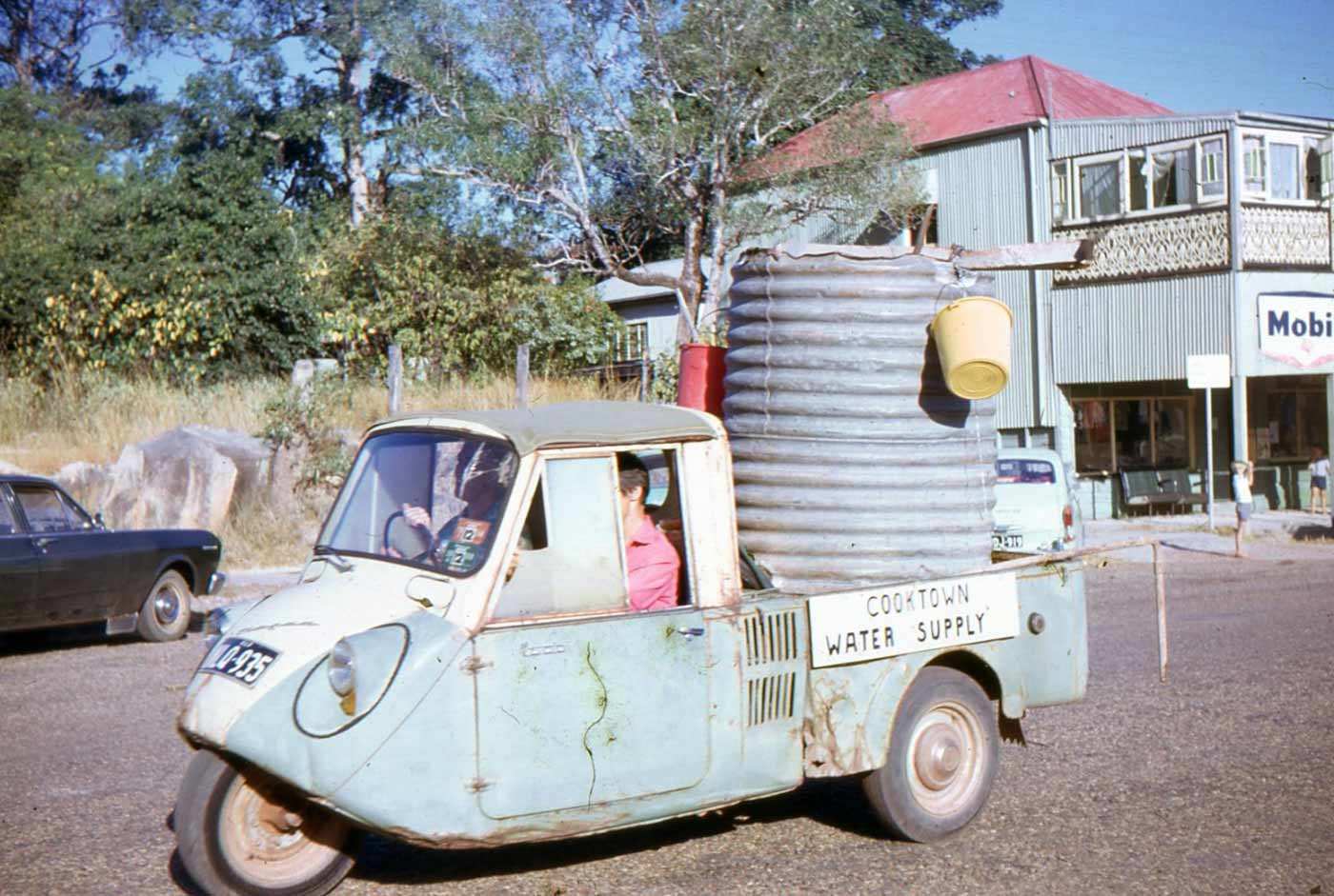 Colour photo and old blue vehicle carrying a tin water tank. On the side of the vehicle is a sign that reads 'COOKTOWN WATER SUPPLY'. - click to view larger image