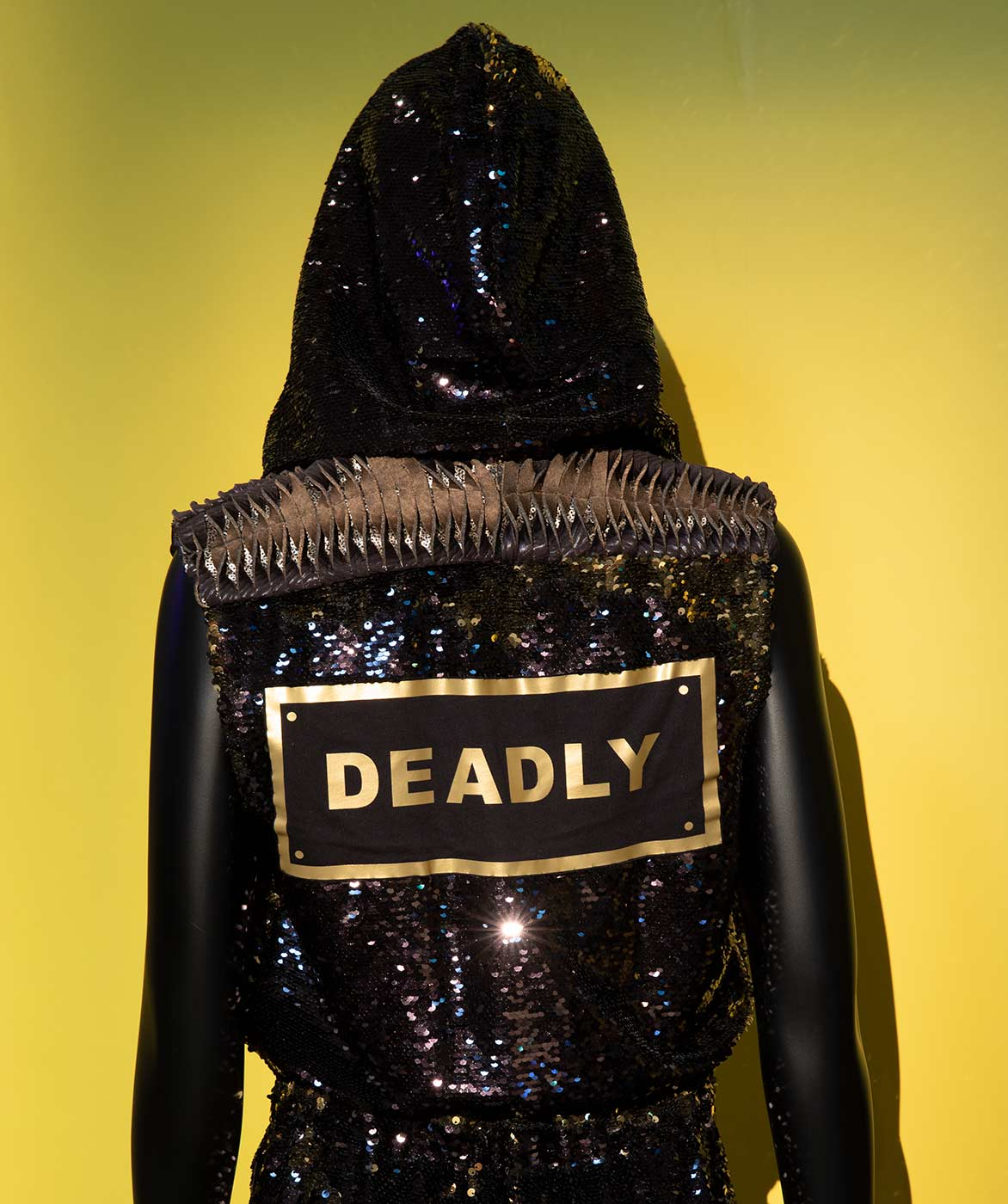 Rear view of a mannequin wearing a black sequinned jumpsuit and hood. On the back, a printed patch says 'DEADLY' in gold letters. - click to view larger image