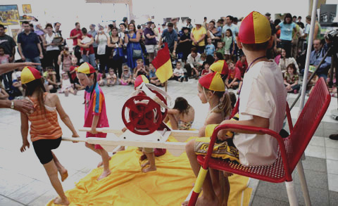 A crowd of spectators in the Museum's Hall watch a group of children pretending to be lifesavers. The children are wearing red and yellow swimcaps and carrying a surf-reel.