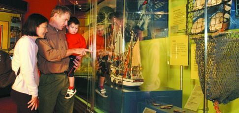 Junie, Tom and Conor Ryan explore the Paipa exhibition in the First Australians gallery