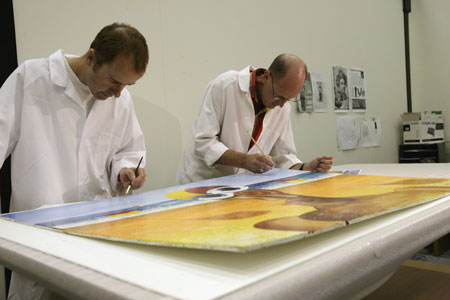 Museum conservators David Parker and Peter Bucke remove debris from the surface of the paintings using soft brushes.