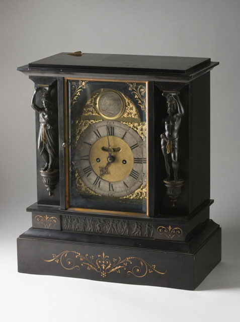 A mantelpiece clock, showing the face and one of the sides. The clock is made from dark material and has carved decorations.