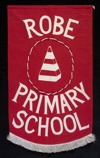 A red banner with a white fringe at the base, set on a black background. The words read 'ROBE PRIMARY SCHOOL'. The banner also features a central image of a red and white striped obelisk.