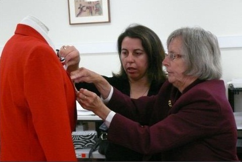 Two women at the right of the image extend their arms to arrange a badge and scarf on a mannequin at the left. The mannequin is dressed in a red jacket.