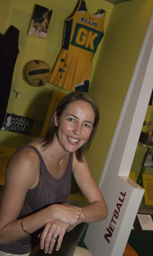 Liz Ellis sits in front of display case showing imagaes, netball and green and gold 'Ellis GK' uniform.