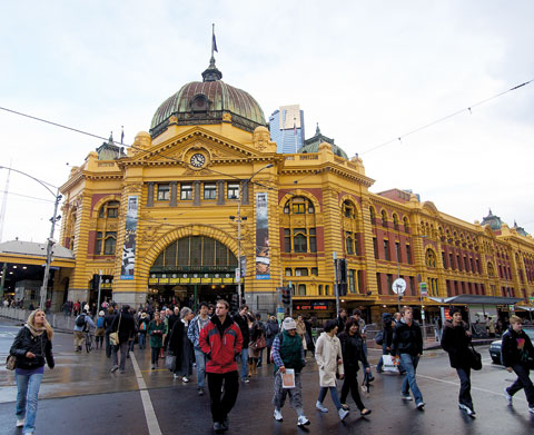 A crowd of people walks across a paved road outside Flinders Street Station, an Edwardian baroque building with a golden-coloured and red brick facade. Tram lines extend in various directions above the road.