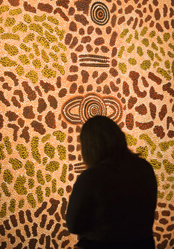 Rear view silhouette of a visitor looking at a dot painting.