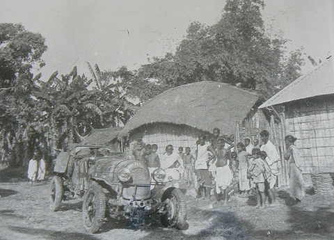 Black and white photo showing an open-topped car in a village. A group of about 20 people stands to the right and several grass walled buildings and trees form a backdrop.