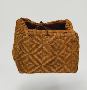 Basket made of pandanus leaves of yellowish and brown strips with a torn handle of plaited coconut fibre.