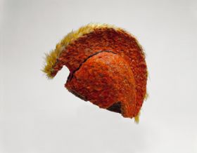Feathered helmet that consists of wicker-work to which red, yellow, and black feathers are attached. A crest on the outer surface extends from the front to the back of the helmet.