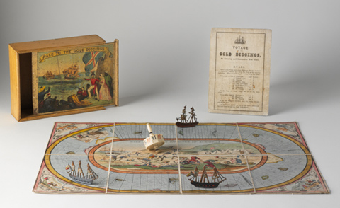 A hand-coloured lithographic playing board made of eight paper sections mounted on linen, with a polygonal twelve-sided teetotum or spinning dice and three small painted metal playing pieces in the shape of tall ships. A varnished wooden box and a instruction sheet have been placed beside the game board.