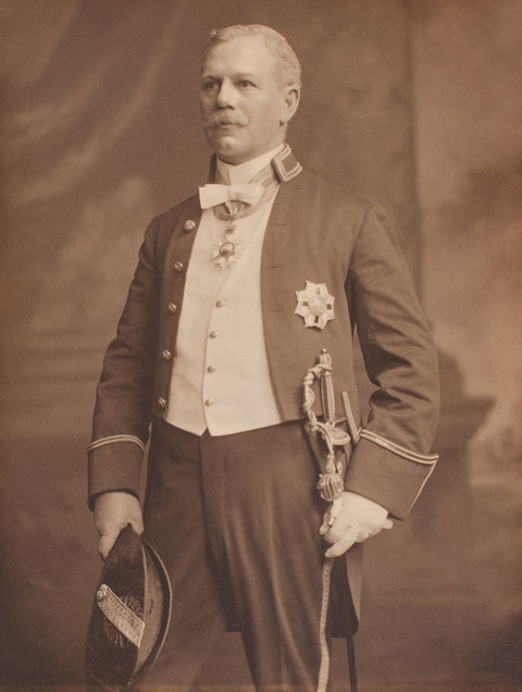 Black and white photograph of a man wearing a ceremonial dress uniform. The man wears ceremonial regalia and holds a bicorn hat in his left hand and a sword in his right.