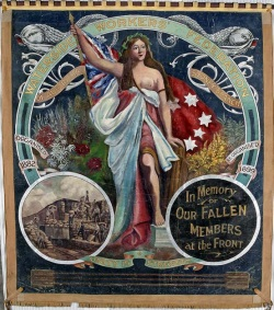 Large, almost square shaped banner painted in oil colours and showing a central image of a woman wearing loose flowing robes. She holds the red ensign and stands among native flowers. The text at the top reads 'Waterside Workers' Federation of Australia, Sydney branch'. An inset image at the bottom left shows workers handling numerous sacks and an inset at the bottom right reads 'In Memory of OUR FALLEN MEMBERS at the Front'. The motto 'Unity is Strength' joins the two insets.