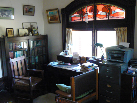 A room with a table, bookcase, filing cabinet and two chairs. The table faces a window that has a red, blue and purple stained glass feature above it. On the table are books, boxes, a tall lamp, a modern keypad telephone and loose papers. There are photographs on the bookcase and paintings hung on one wall.