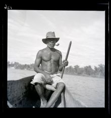 A black and white photographic negative that depicts an Aboriginal man wearing a hat with a pipe in his mouth sitting in a canoe on a river.