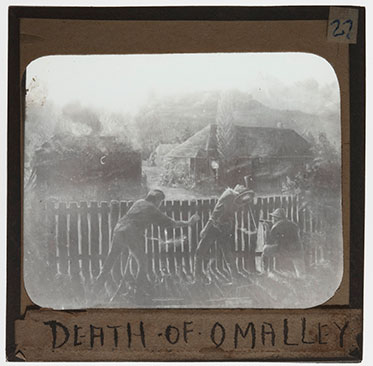 Black and white image of three men crouching behind a fence. The man at centre is reeling backwards. A building burns in the distance. 'DEATH OF O'MALLEY' is handwritten at the bottom of the slide.