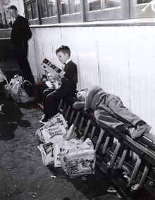 Black and white photograph showing two young boys, one lying with his eyes closed, on a ladder which rests longways, alongside a wall. Several show bags are lined up beneath him. Beside him, another boy sits reading.