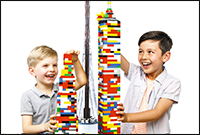 Two boys each holder a tower made from Lego.
