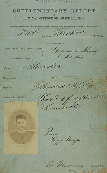 A stained form completed in copperplate handwriting. Under the heading 'Offence' the word 'Murder' has been written. A photo of Ned Kelly appears bottom left.