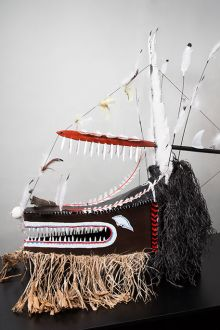 Large cultural mask with brown, white and red tones, feathers and other materials.