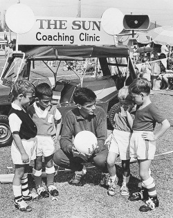 Black and white photo showing a man dressed in a tracksuit, squatting at the same level as four young boys. The man is ressed in a dark tracksuit and boots and holds a white soccer ball. Behind him is a small soft-topped vehicle with a sign on top which reads 'THE SUN / Coaching Clinic'.