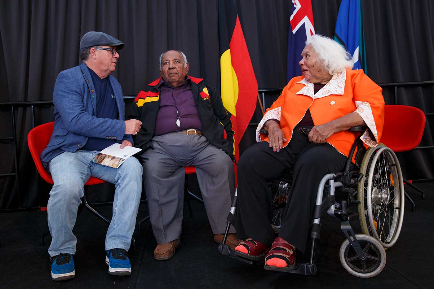 Two men and a woman in a wheel chair, on a stage - click to view larger image