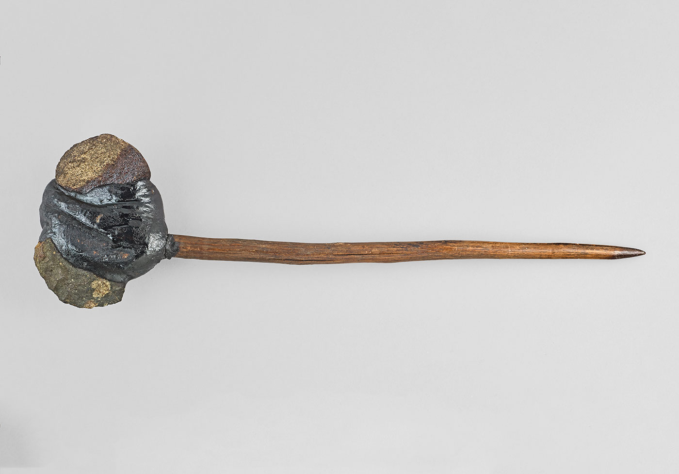 An axe with a tapered wooden handle and stone head with resin. - click to view larger image