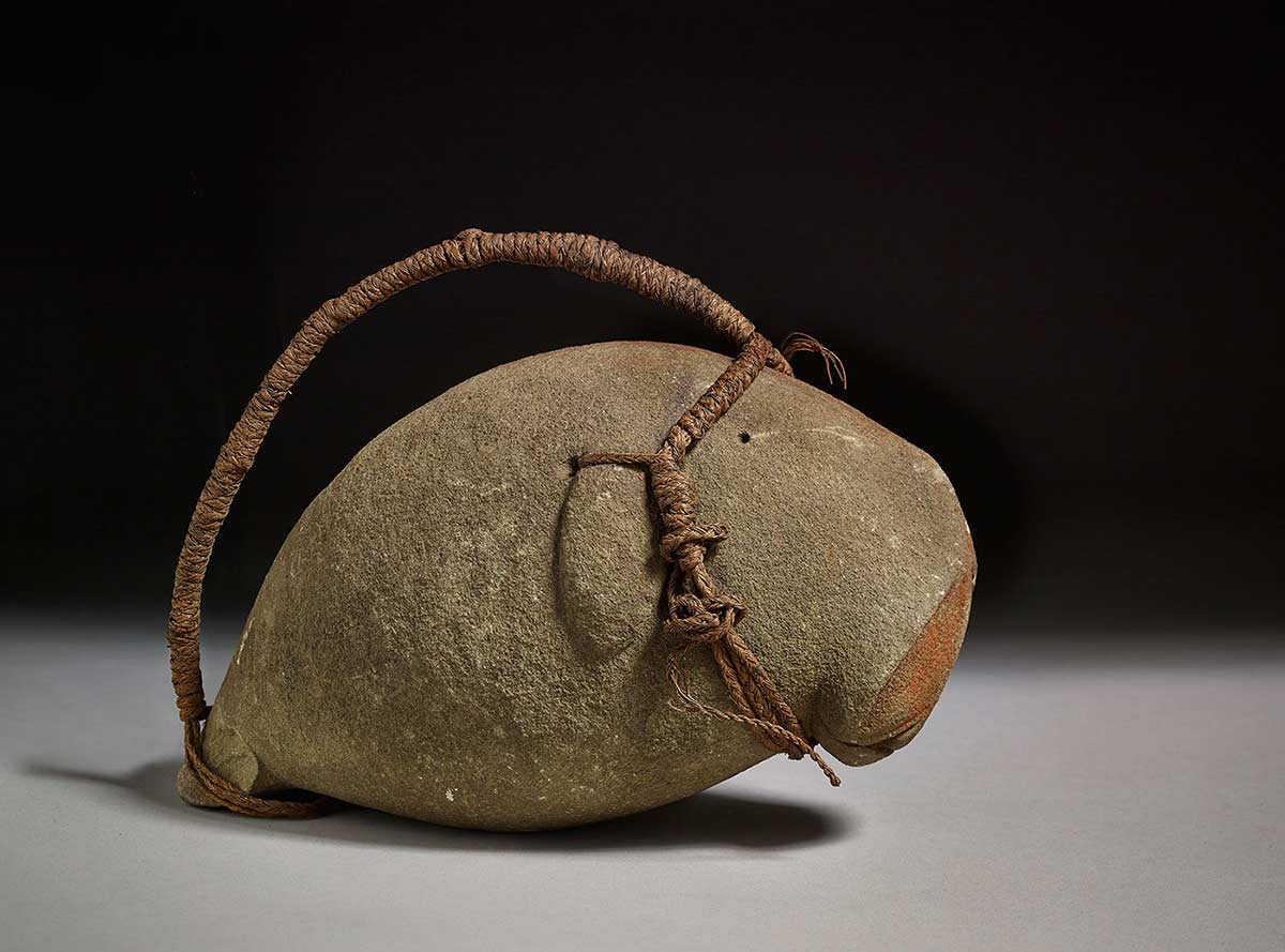 Charm resembling a dugong made from stone, ochre and fibre.