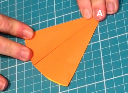 Fingers hold down a piece of orange paper. The letter B in white font is superimposed on the top left corner of the paper and the capital letter A (also in white font) is superimposed on a pointy end in the centre. A few centimetres to the left is a small block of black text in capital letters which reads 'curved edge' with an arrow pointing to the curved edge of the paper.