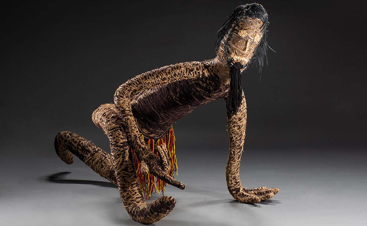 A sculpture of a figure featured crouching down on one knee with one elbow resting on the right knee and the left hand on the ground. The sculpture is made of various plant-based and synthetic materials. - click to view larger image